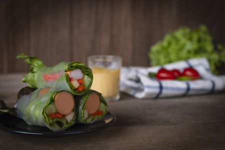 Salad rolls on black plate placed on a wooden table with salad dressing, White Blue Striped Fabric, lettuce and tomato placed backside.