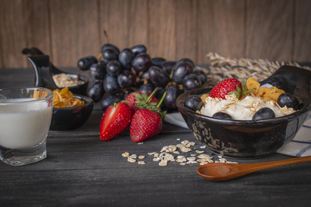 Yoghurt mix oatmeal, strawberry and grape topping in black bowl on wood table with Blue and white striped fabric, spoon, strawberry, milk in glass, grape, cornflakes and oatmeal placed around.