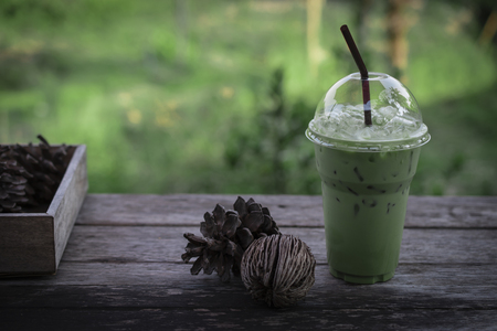 Iced milk green tea drink with dried pine cones on wooden table against green nature background