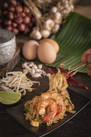 Thai fried noodles or pad thai with shrimp on black plate placed on the wood table there are eggs, garlic, bean sprouts, shallot, silver water bowl, chilli and cutting board placed back side. Use fork to shovel noodles. Banco de Imagens - 119950605
