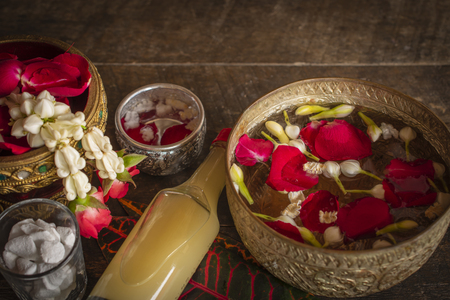 Red rose, Jasmine and popped rice on the calm water surface placed on the wood table Ready for pour water on the hands of revered elders and ask for blessing.