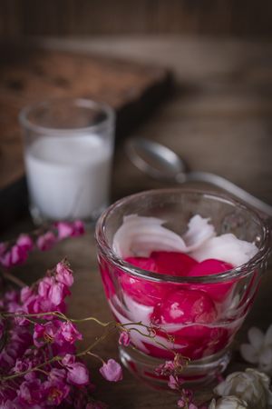 Thapthim krop, mock pomegranate seeds in coconut and syrup in the glass on the wood table there are flower, spoon and coconut milk placed around.