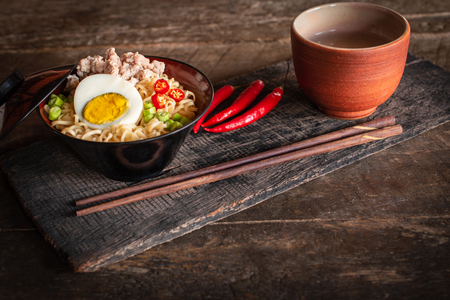 Instant noodle with pork, egg and vegetables on black bowl on the wood table there are chilli, chopstick and drinking glass placed around. 版權商用圖片
