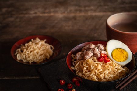 Instant noodle with pork, egg and vegetables on black bowl on the wood table there are chilli, chopstick, instant noodle in black plate and drinking glass placed around.