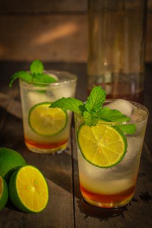 Frisches Eis-Honig-Zitronen-Soda-Getränk auf dem Holztisch gibt es Zitronenscheibe, das gleiche Objekt und Honig in einer Glasflasche. Standard-Bild