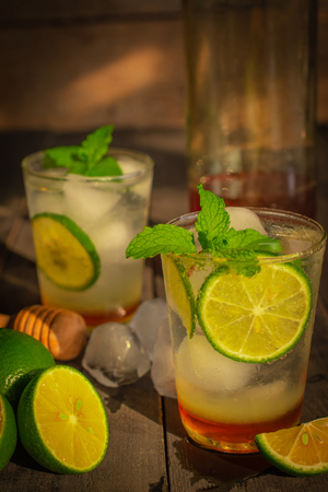 Fresh Ice Honey Lemon soda drink sul tavolo di legno ci sono fetta di limone, ghiaccio, miele in bottiglia di vetro e mestolo di miele in legno disposti intorno.
