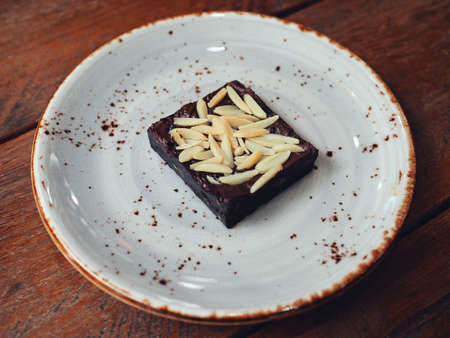 Variety of Brownies include Almond Macadamia Peanut and Chocolate Chip on the white dish and wood table from above view Stock Photo