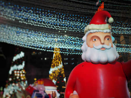Big Santa Claus figure from front view in Christmas festival at night with Christmas Tree background. Can use for background and have copy space to add text.