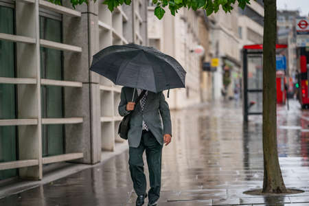 Middle-aged businessman wearing a suit caught out in the rain during a windy  drizzly day fighting the wind under an umbrella in Holborn, London during the COVID-19 pandemic 101 新闻类图片