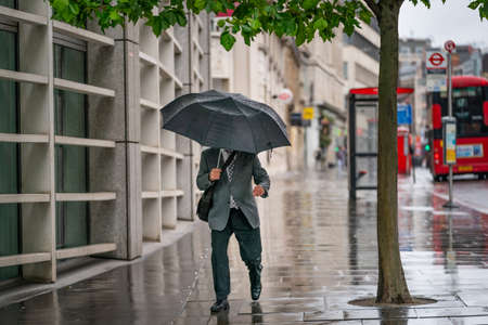 Middle-aged businessman wearing a suit caught out in the rain during a windy  drizzly day fighting the wind under an umbrella in Holborn, London during the COVID-19 pandemic 100 新闻类图片