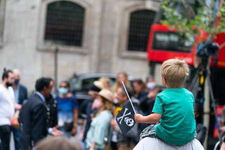 LONDON, ENGLAND - JULY 28, 2020: A young boy fan waving a Jolly Roger skull and crossbones flag outside the Royal Court of Justice in the Johnny Depp defamation libel Trial against The Sun Newspaper - 829 Editöryel