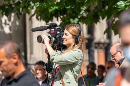 LONDON, ENGLAND - JULY 28, 2020: Beautiful female camerawoman wearing headphones filming for the press at the Royal Courts of Justice, The Strand, London - 295 Editorial