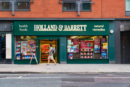 LONDON, ENGLAND - JULY 24, 2020: Holland & Barrett health food store at Holborn, London during the COVID-19 pandemic with a man walking in front wearing a face mask - 061