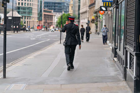 LONDON, ENGLAND - JUNE 3, 2020:  Rear view of a young male asian traffic warden wearing an uniform during the coronavirus COVID-19 pandemic walking along Holborn, London, England looking for car parking offences - 044