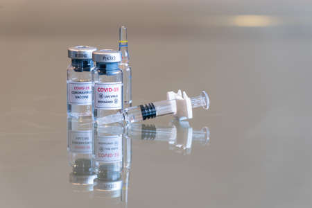 A closeup double vial set of COVID-19 Coronvavirus live virus biohazard culture with a syringe on the right and needle tip in the front - 122 Stock fotó