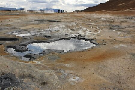 Puddles reflecting a cloudy sky on the solfatara fileds of Kafla mountains, Iceland Standard-Bild