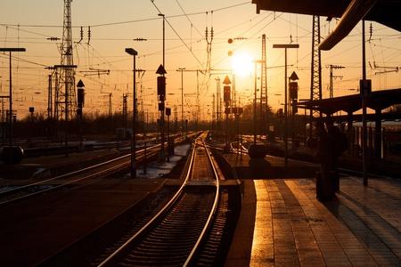 despedida: Winter puesta de sol sobre Karlsruhe estaci�n de tren con la gente espera de un tren