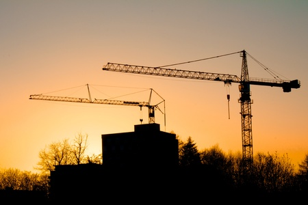 Sunset behind buildings and cranes in Freiburg, Germany photo