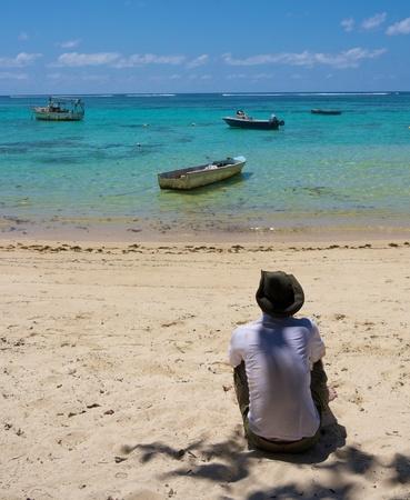 royale: Hombre solo con un sombrero sentado en la playa blanca de Anse Royale, Isla de Mah�, Seychelles, mirando a lo lejos con algunos barcos en primer plano Foto de archivo