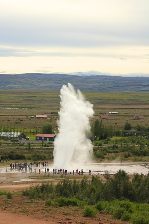 Famous Iceland Strokkur geyser erupting with tourists watching