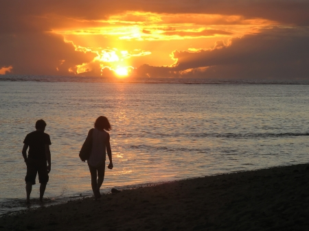 Happy couple walking in the sunset at Mauritius beach