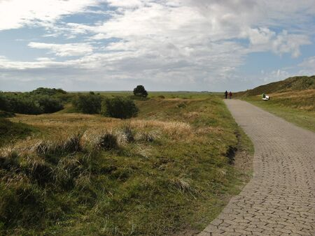lonesome: Two hikers on a rural road between grassy hills on Spiekeroog island, Germany