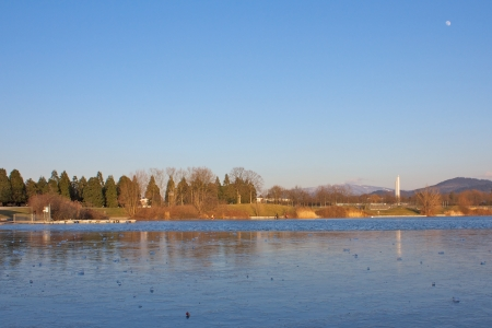 Wide shot of the frozen Freiburg Seepark lake and church with the moon shining from above Stock Photo - 15445000