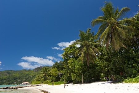 royale: Quiet beach with just a few people and a church in the background at Anse Royale bay, Mahe island, Seychelles