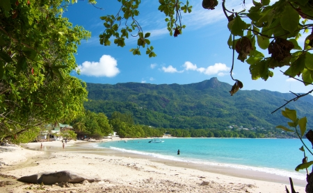 View over the amazing Beau Vallon bay with a few people walkingalong the white beach on Mahe island, Seychelles