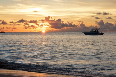 Fishing boat going towards a romantic and colorful sunset over the Indian Ocean shores of Beau Vallon bay, Mahe island, Seychelles Stock Photo - 15450944