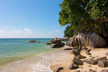 Typical granite rocks on a quiet and romantic part of Beau Vallon beach on Mahe island, Seychelles