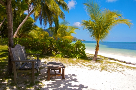 praslin: Wooden bench and footrest at the white sands beach of the Indian Ocean, Praslin island, Seychelles