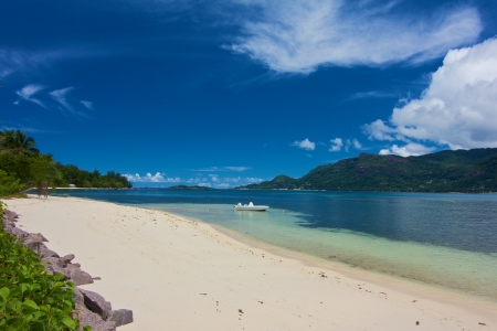 Lonely dream beach with white sands, clear water and a boat on Cerf island, Seychelles Stock Photo
