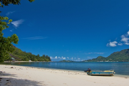 Lonely white beach with a motor boat and the lush green forests and blue waters of the Indian Ocean on Cerf island, Seychelles photo