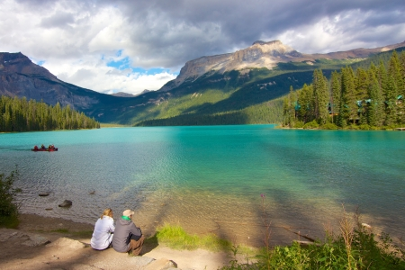 Couple looking out on beautiful Emerald Lake at dusk Stockfoto