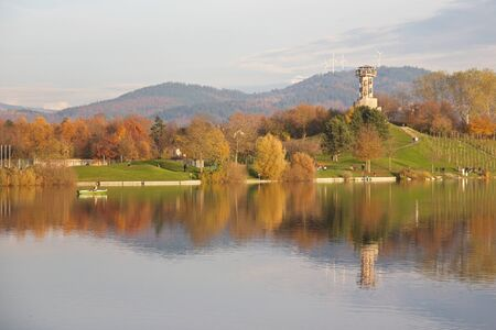 Autumn scene at a German lake with people walking and a watchtower reflecting in the water