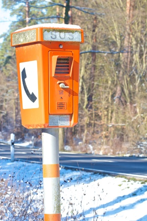Orange emergency phone standing next to a dangerous and accident-prone winter road in Germany Stock Photo - 17921886