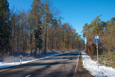 important phone call: Lonely forest road in winter with a German road sign to indicate a nearby emergency phone Stock Photo