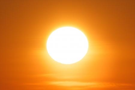 Colorful sun in a clear orange sky