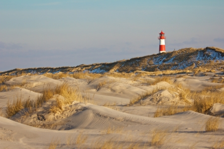 Beautiful sand dune scene with a lighthouse in the background