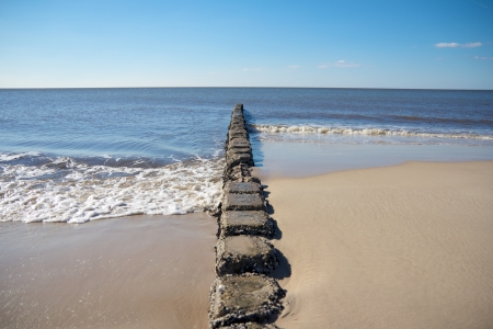 Rocky North Sea groin leading into the water breaking the waves geometrically Stockfoto