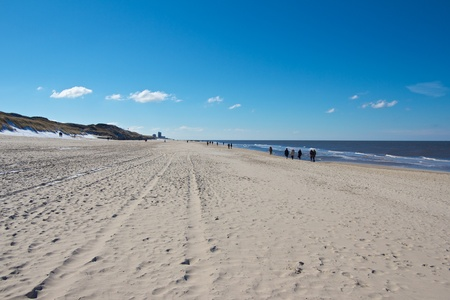 Hikers walking along a wide Nort Sea beach towards Westerland city on Sylt island, Germany photo