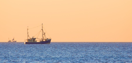 Fish trawler on the distance against a clear dusk sky over the North Sea