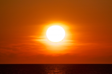 Colorful sun in a clear orange sky reflecting on the ocean beneath