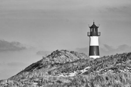 Beautiful sand dune scene with a lighthouse in the background - monochromatic version photo