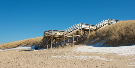 Wooden staircase  between grassy dunes leading down to a North Sea beach photo