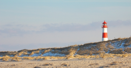 Beautiful sand dune scene with a lighthouse in the background photo