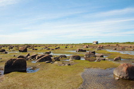 View over the stone desert of Hudson Bay, Canada, during low tide with a cabin in the distance photo