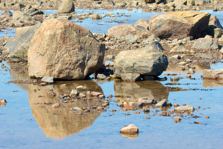 View on two rocks of Hudson Bay, Canada, during low tide with reflections in the shallow waters photo