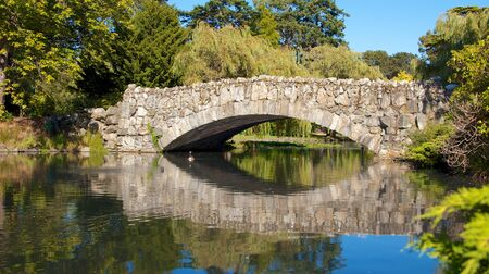 Romantic old stone bridge over a pond in a park in Victoria, Vancouver Island, Canada photo
